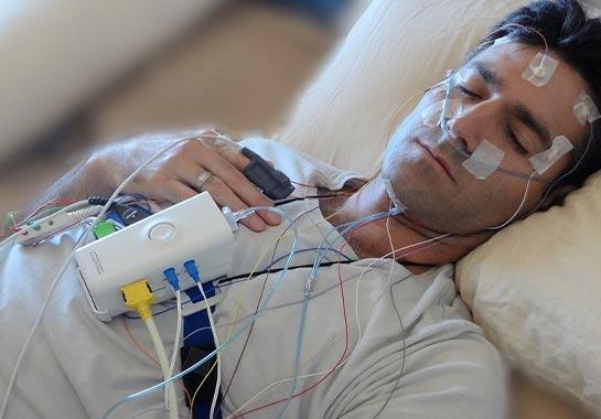 Homem realizando polissonografia, com equipamento no peito e vários fios colados na pele por fitas - Clínica do Pulmão