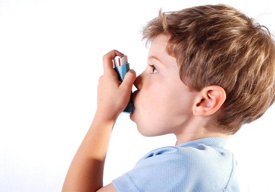 Menino de 7 anos usando spray para asma - Clínica do Pulmão