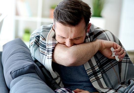 Homem com rosto protegido pelo cotovelo porque está espirrando - Clínica do Pulmão