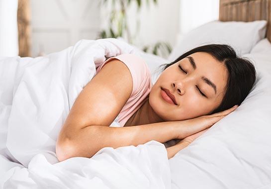 Mulher asiática dormindo em lençóis brancos - Clínica do Pulmão