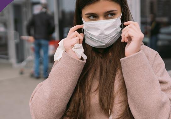 Mulher branca de máscara com roupas quentes típicas de inverno - Clínica do Pulmão