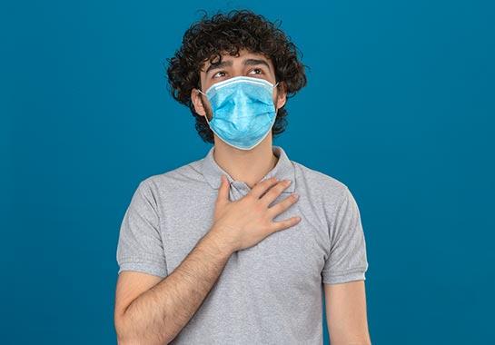 Homem branco com máscara e mão do peito - Clínica do Pulmão
